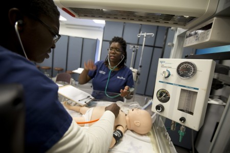 "<a href=""/academics/accelerated-options/bsn-second-degree/"">Second degree</a> nursing students Jacqueline Harper and Linda Schnolis examine a simulated newborn lying in a baby warmer shortly after its birth as part of their <em>Nursing Care of the Pediatric Patient</em> course."