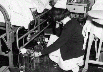 Nurse examining chest tube drainage bottles, Hospital of the University of Pennsylvania, 1972
