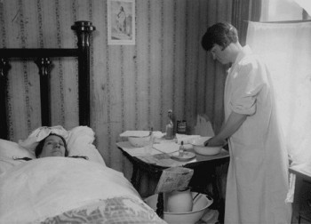 Typhoid patient in bed receiving care from a visiting nurse, Visiting Nurse Society of Philadelphia, c. 1925
