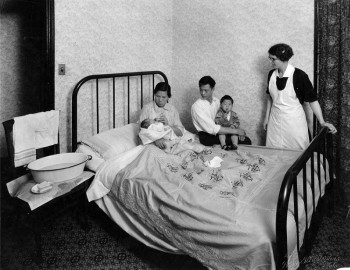 A visiting nurse oversees as mother bottlefeeds her infant while father and son look on, Visiting Nurse Society of Philadelphia, c. 1930