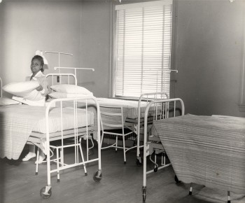 Nursing assistant preparing beds for patients, Frederick Douglass Hospital, Philadelphia, PA c. 1945