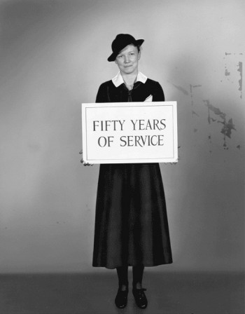 "Visiting nurse holds ""Fifty Years of Service"" sign for the cover of a pamphlet celebrating the Visiting Nurse Society of Philadelphia's anniversary, 1936"