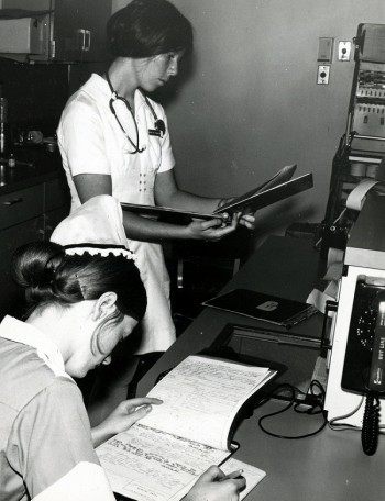 Registered nurse and student nurse in ICU (Intensive Care Unit), Philadelphia General Hospital, c. 1970