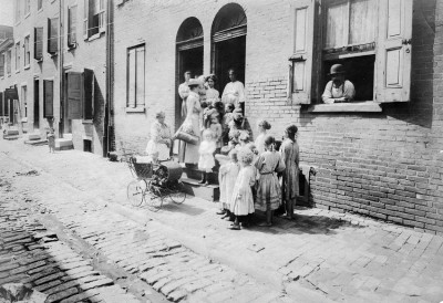 Visiting nurse entering a row home surrounded by children and adults, Visiting Nurse Society of Philadelphia, c. 1890